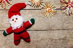 Santa claus puppet and straw stars on wooden table Stock Photos