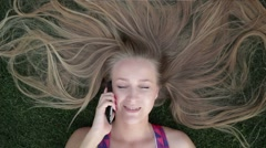 Girl with beautiful blonde hair lying on grass Stock Footage