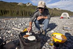 MIddle-aged man cooking pancakes over firebox while camped on Nahanni River, Stock Photos