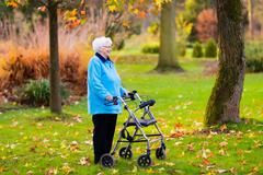Senior lady with a walker in autumn park Stock Photos