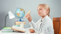 Portrait schoolgirl 7-8 years sitting at the table and looking at sweet wafer Stock Footage