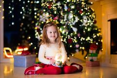 Little girl holding snow globe under Christmas tree Stock Photos
