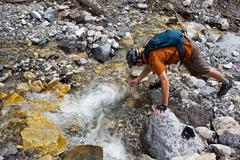 A man filling up his water bottle out of a mountain stream while mountain biking Stock Photos