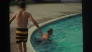 1974: childrens are playing in a swimming pool and a boy jumps to swim LYNBROOK, Stock Footage