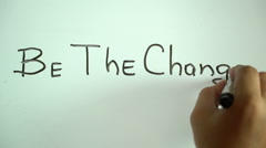"""Hand writing title """"Be the change"""" using a black marker on a white board Stock Footage"""