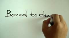 "Hand writing title ""Bored to death"" using a black marker on a white board Stock Footage"