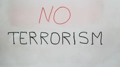 "Hand writing a ""No terrorism"" message on a white board using a black marker Stock Footage"