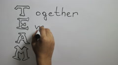 "Hand writing a ""Team"" message on a white board using a black marker Stock Footage"