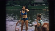 1974: a girl wearing a bikini jumping into a lake with ease LYNBROOK, NEW YORK Stock Footage