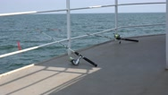 Fishing rods lie on iron deck of vessel on background of sea water Stock Footage