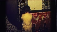 1974: a child in pajamas in the living room standing at a small brick fireplace Stock Footage