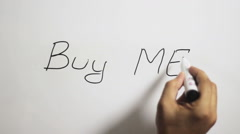 "Hand writing a ""Buy me"" message on a white board using a black marker Stock Footage"