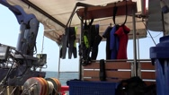 Diving suit and scuba diving equipment land on stern ship walking on sea Stock Footage