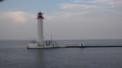 White lighthouse on a pier against the sea in the mist Stock Footage