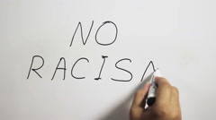 "Hand writing a ""No Racism"" message on a white board using a black marker Stock Footage"