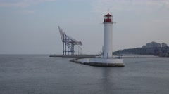 View of white lighthouse on pier in background of cranes at port Stock Footage