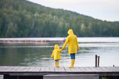 Woman holding her little son by hand while he looking into water Stock Photos