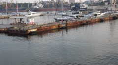 Approaching pier for mooring in seaport against backdrop of yachts Stock Footage