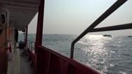 View through railing ship on the horizon with cargo ship Stock Footage