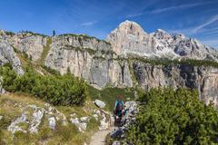 A female hiker on a trail in the Dolomite mountains in northern Italy. Stock Photos
