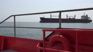 View through railing ship on the horizon with cargo ship Stock Footage