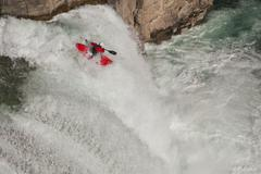 A male kayaker runs leap of faith, a 30 foot waterfall on the Upper Elk River, Stock Photos
