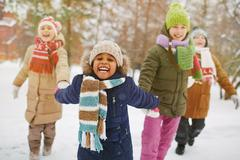 Happy girl holding her friends by hands in snowfall Stock Photos