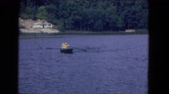 1964: engaged with a partner in a watery fun game in the middle of a lake  Stock Footage