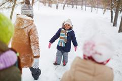 Ecstatic child in winterwear looking at camera surrounded by her friends Stock Photos