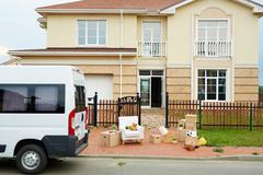 Van and packed things in front of new house outdoors Stock Photos