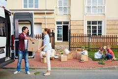 Young man giving his wife box while unloading things from van Stock Photos