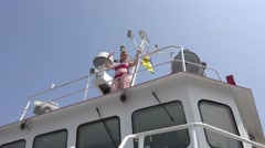 Woman in swimsuit on upper deck of research vessel looks into distance Stock Footage