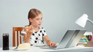 Girl 7-8 years laughing eating bread with jam butter and using laptop sitting Stock Footage