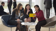 4K Female business team in discussion in busy meeting area of modern office Stock Footage