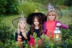 Spooky girls dressed as witches looking at camera Stock Photos