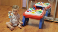 Baby sits on the floor in the room and play. Stock Footage