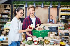 Happy young couple choosing pickles in supermarket Stock Photos
