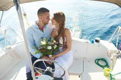 Amorous bride and groom traveling on yacht during honeymoon Stock Photos