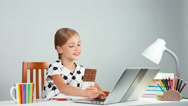 Girl 7-8 years using laptop and eating chocolate. Child holding a chocolate Stock Footage