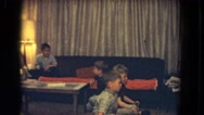1964: four kids are sitting on the floor and couch to watch something  Stock Footage