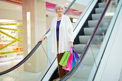 Smiling senior woman with paperbags descending on escalator Stock Photos