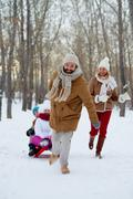 Happy man pulling sledge with his two kids Stock Photos