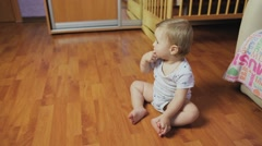 Baby boy sitting on the floor in the room. Stock Footage