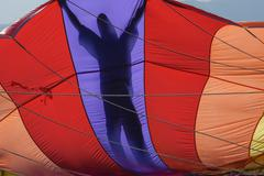 A parasailing crew member is silhouetted holding a parachute preparing to lift a Kuvituskuvat