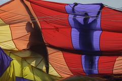 A parasailing crew are silhouetted holding a parachute preparing to lift a Kuvituskuvat