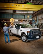 Tradesman holding crane hoist in an industrial workshop Stock Photos