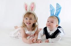 Cute young boy and girl wear bunny ears while looking up and smiling Stock Photos