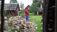 Gardener guy preparing natural wood fuel and rural houses. 4K Stock Footage