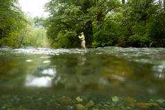 A young woman fly-fishing for trout on the Saloompt River, Bella Coola, British Kuvituskuvat