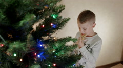 Cute boy eat gingerbread man near new year tree and hanging it back to the tree Stock Footage